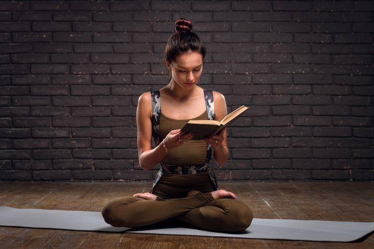 девушка читает книгу по йоге