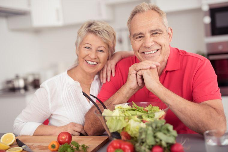 пожилая пара готовит обед