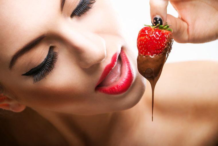 девушка ест клубнику с шоколадом