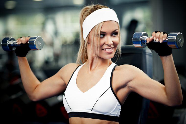 девушка делает упражнения с гантелями для похудения