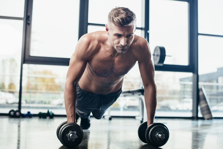 мужчина выполняет упражнения с гантелями