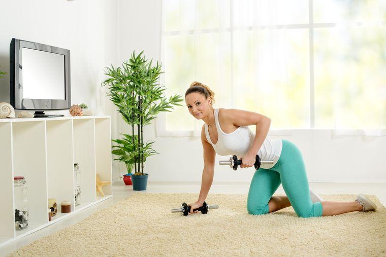 девушка делает упражнения с гантелями
