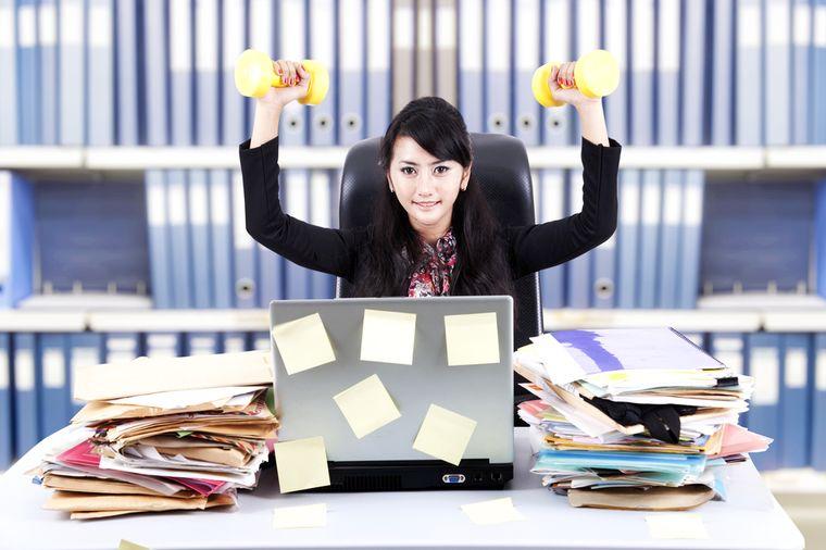 девушка с гантелями в офисе